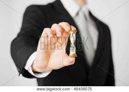 close up of man hand holding hourglass.