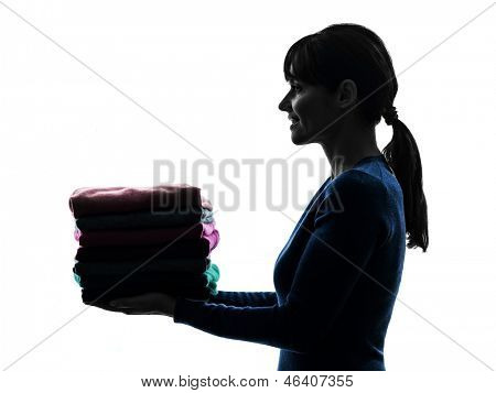 one caucasian woman maid holding sweater pile cleaning  in silhouette studio isolated on white background