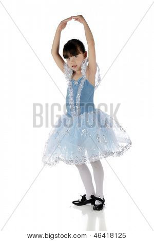 A beautiful young girl in a tap-dancing pose in her tap dancing shoes and blue and silver dress.  On a white background.