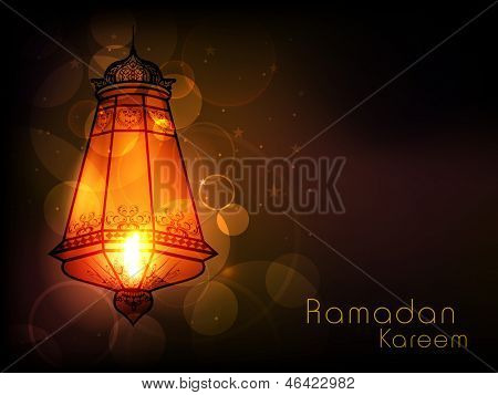 Illuminated intricate Arabic lamp on abstract background for Ramadan Kareem.