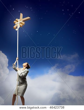 Image of businesswoman climbing the rope attached to yen sign