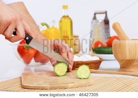 Fresh vegetables being cut with a knife