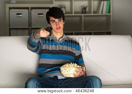 young man watching television with popcorn