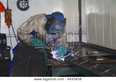 Labourer Arc Welding A Sheet Or Piece Of Metal
