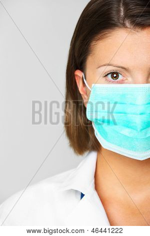 A portrait of a female doctor in a mask over grey background