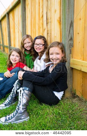 Girls group in a row smiling sitting in a wooden fence outdoor