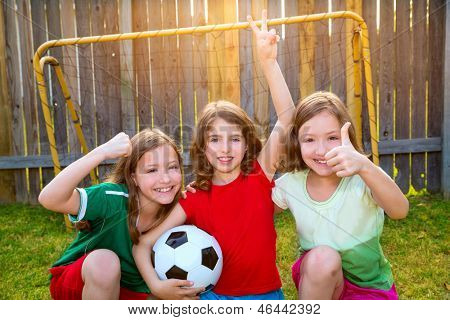 three sister girls friends soccer football winner players on the backyard
