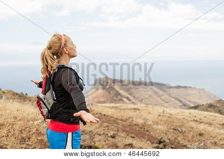 Woman Runner, Arms Outstreched In Mountains