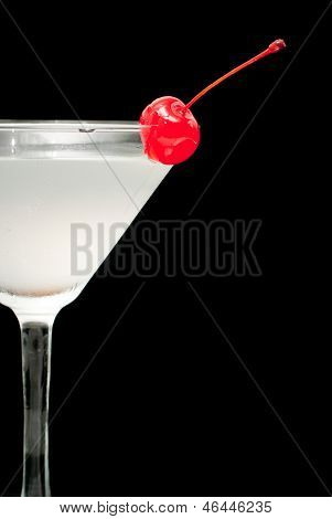 cocktail in martini glass with red cherry closeup