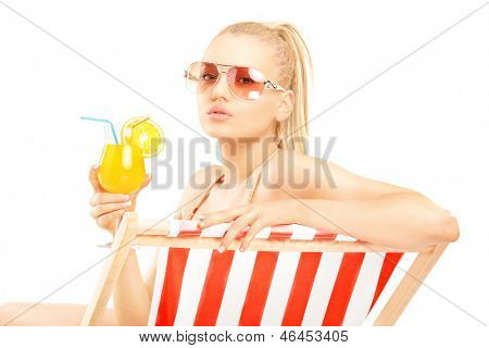 Attractive blond female sitting on a sun lounger and drinking a cocktail, isolated on white background