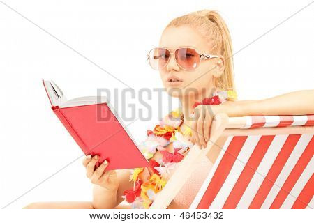 Attractive blond female sitting on a sun lounger and reading a book, isolated on white background
