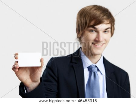 Young businessman showing and pointing to a business card, over a gray background