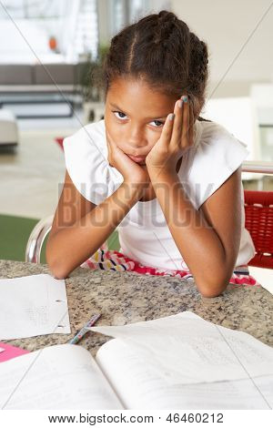 Fed Up Girl Doing Homework In Kitchen
