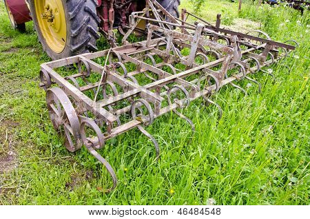 Tractor On Farm Field Gras With Metal Harrow