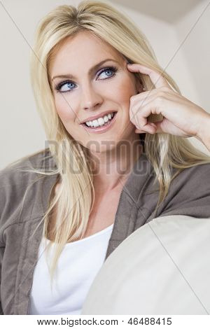 Portrait of a beautiful happy blond woman with blue eyes smiling and looking up
