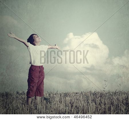 Free child dreaming with outstretched hands on beautiful meadow with clouds in background