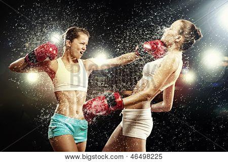 Two young pretty women boxing standing against flashes background