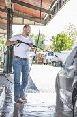 stock photo of pressure-wash  - Bald man with a beard is washed with a pressure washer be black car on a sunny day - JPG