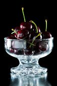 image of bing  - glass bowl filled with ripe red bing cherries isolated on a black background - JPG