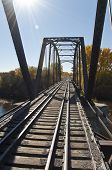 stock photo of trestle bridge  - A trestle bridge spans a river in the Fall season - JPG