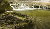 image of shale  - Time Lapse Stream with a chunk of brittle shale rock in the foreground - JPG