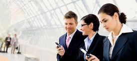 picture of mobile-phone  - Happy businesspeople using mobile phones at office lobby  - JPG