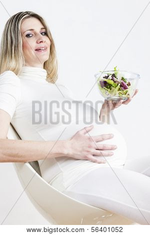 portrait of pregnant woman with vegetable salad