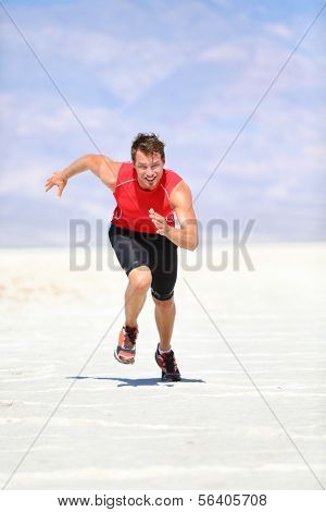 Runner - man running sprinting outdoor in desert nature. Fit athlete in fast sprint run at great speed towards camera. Male fitness model training and working out in amazing extreme desert landscape.