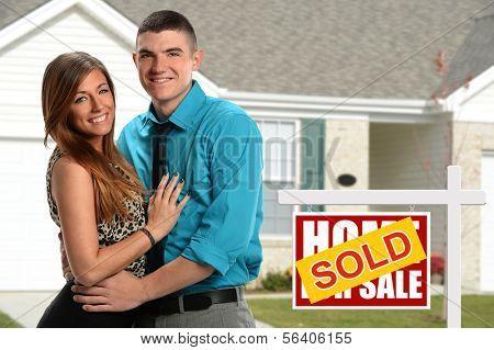 Pareja joven frente a su casa recién adquirida
