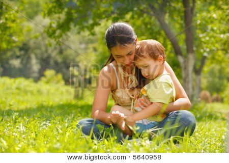 Happy Mother And Son Sitting In A Meadow