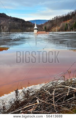 A Flooded Church In A Toxic Red Lake. Water Polluting By A Copper Mine