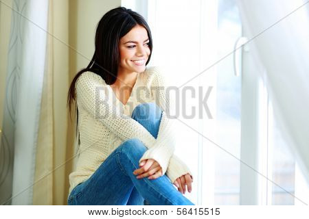 Young cheerful woman sitting on a window-sill and looking outside