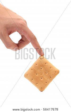 Hand holds saltine soda cracker.