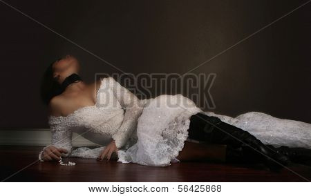 a bride on a hardwood floor with moody lighting