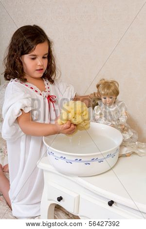 Adorable little victorian girl washing her vintage doll