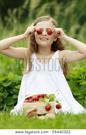 Strawberry time - young girl with picked strawberries in the garden