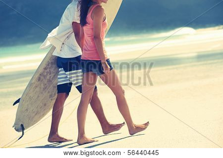 Hispanic couple walk on beach together with surfboard having fun outdoors