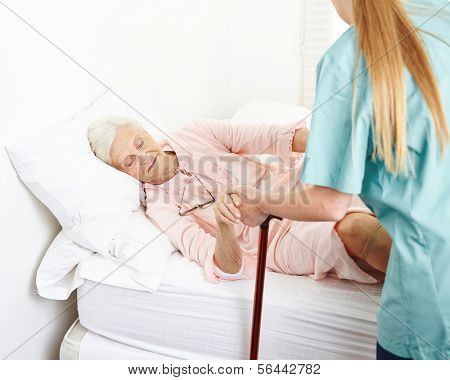 Caregiver helping senior woman in nursing home out of bed