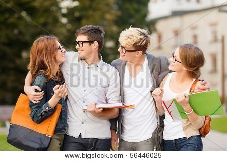 summer holidays, education, campus and teenage concept - group of students or teenagers with files, folders and eyeglasses hanging out