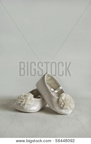 White colored baby shoes with white pom poms.