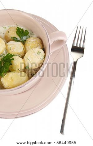 Tender young potatoes with sour cream and herbs in pan isolated on white