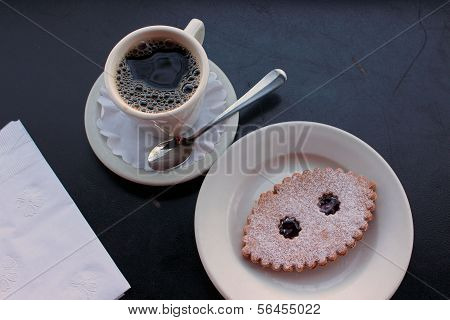 Cup of steaming hot coffee and Linzer cookie