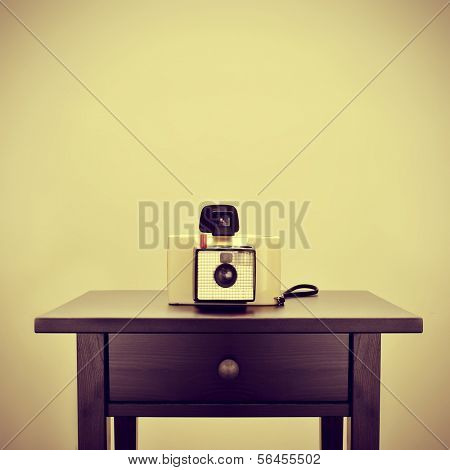 picture of an old instant camera on a bureau, with a retro effect