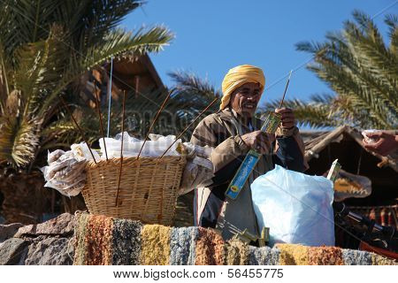 DAHAB - JANUARY 23. Bedouin street vendor selling food on walkway in Dahab, Egypt. Incense sticks drive the flies away.