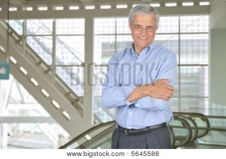Middle Aged Businessman In Building With Arms Crossed