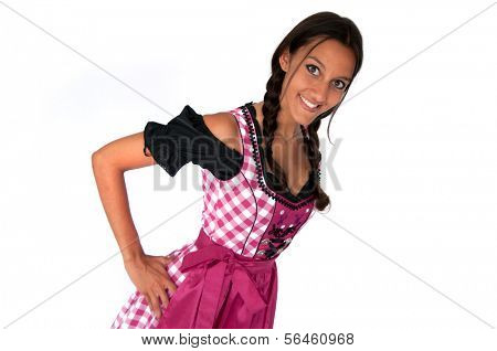 Young woman wearing dirndl standing akimbo on white background