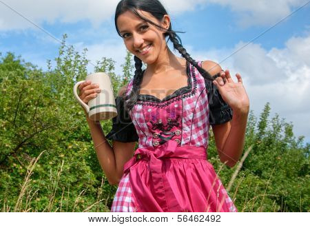 Young woman wearing dirndl posing with beer mug in the field
