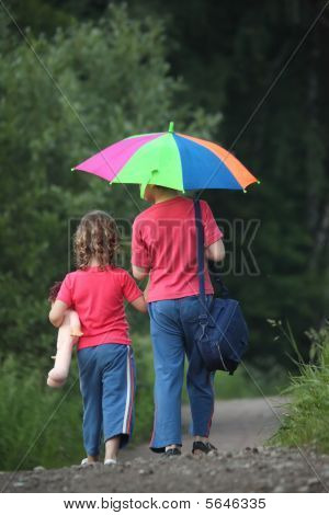 Boy And Girl Go For A Walk With Umbrella In Park, Rear View