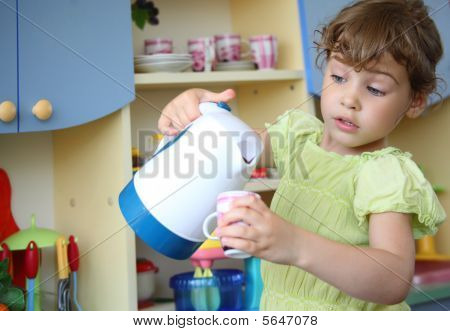 Little Girl With Kettle And Cup In Hands