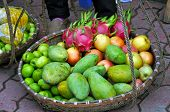 stock photo of peddlers  - Tropical fruits in a basket in a Vietnamese market - JPG